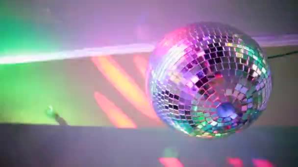 Zrcadlová koule klubu s odrazy světla a pohyb kamery.