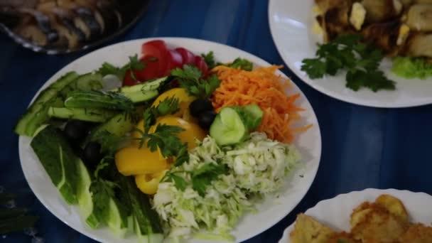 Salát s bylinkami v talíř na stůl a různých masitých jídel