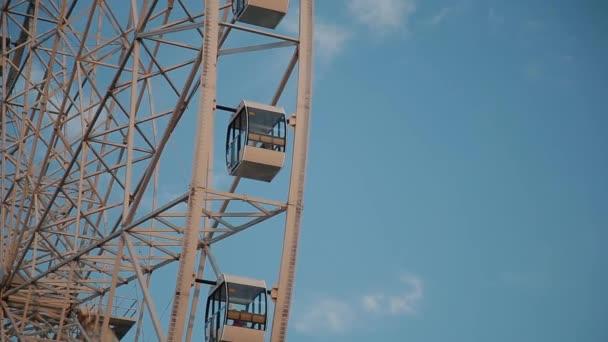Ferris wheel against the blue sky in the amusement park.