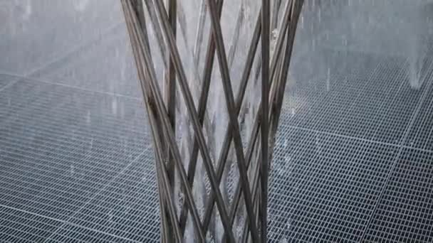 Part of a stainless steel fountain, water pours from the holes in the fountain.