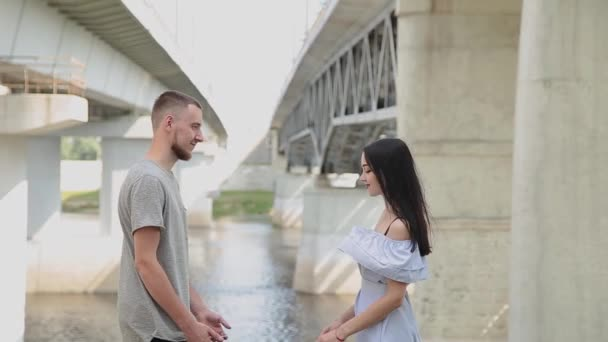 A loving couple are standing under a bridge hugging and kissing