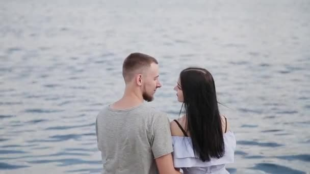 A loving couple sitting by the river kissing and hugging.