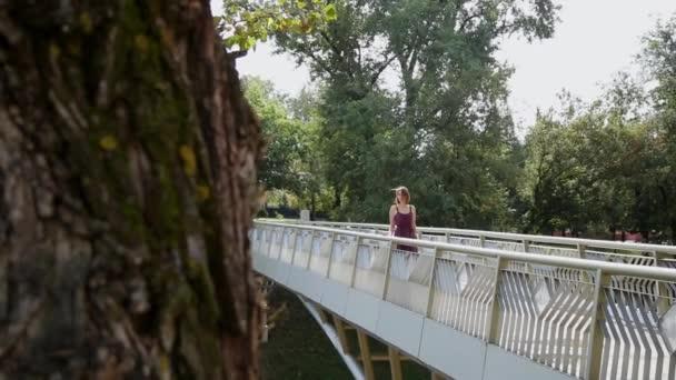 Velmi krásná a sexy dívka je stál na mostě a díval se do vzdálenosti