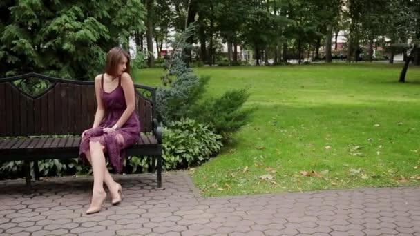 Velmi krásná a sexy dívka, sedící na lavičce v parku