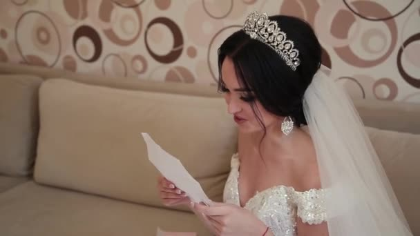 Very beautiful bride opens and reads a letter from a loved one.