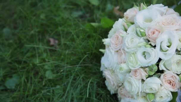 Krásné svatební kytice leží na trávě.