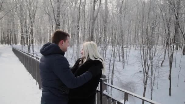 Schönes junges Paar umarmt und redet in einem städtischen Winterpark.
