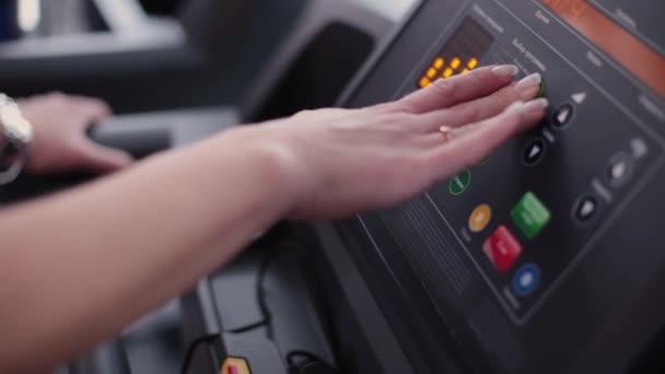 Sehr schöne und sexy Fitness-Modell richtet ein Laufband im Fitnessstudio.