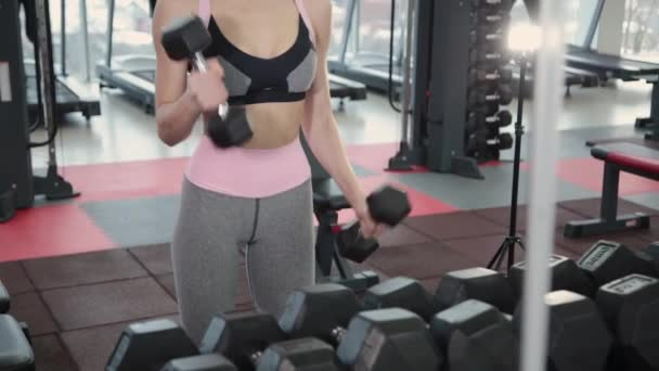 Beautiful athletic young girl trains dumbbells biceps in the gym.