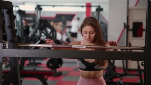 Beautiful athletic young girl coming to the bar for squats in the gym.