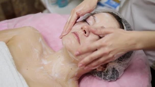 Fürdő nő arc masszázs. Arc masszázs spa szépségszalon. Nő élvezi, ellazító arcmasszázs, kozmetológia spa központban. Testápolás, bőrápolás, wellness, szépségápolás.