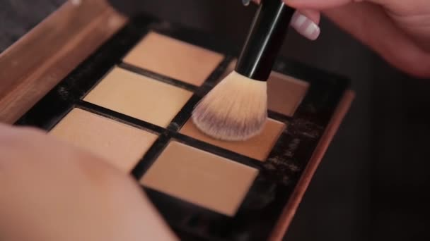 A palette with eye shadows and a makeup brush: womens cosmetics. Morning make-up. Decorative cosmetics: a palette with eye shadows, a brush.Evening make-up.Details of the make-up artists work