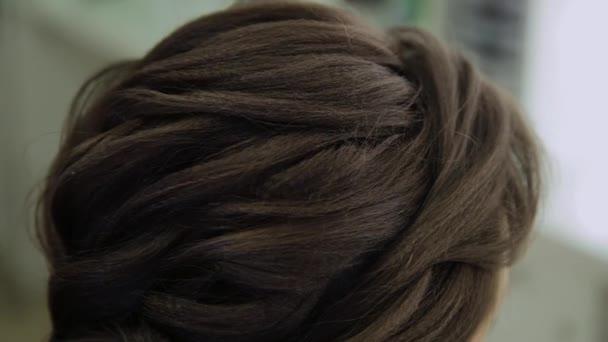 Eine junge Frau sitzt im Friseursessel, ein Friseur frisiert. eine junge blonde Frau kam in den Schönheitssalon, um sich eine stylische Frisur zu machen.