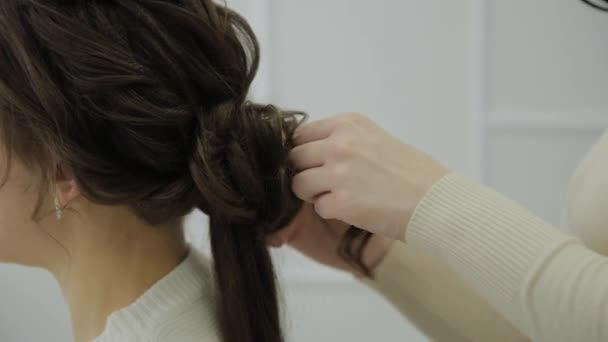 A young woman sits in a hairdressers armchair: a hairdresser does a hair styling. A young fair-haired woman came to the beauty salon to make a stylish hairstyle.