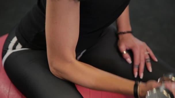 Mladá sportive žena sedící na fit ball a zvedání činek při školení biceps v tělocvičně