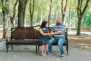 Two people in love sit on a bench in the park.