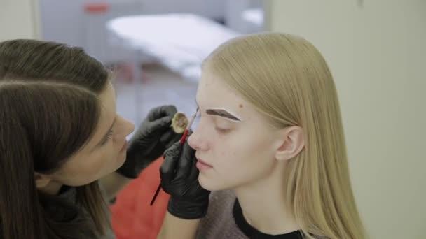 Vizážistka dělá obočí barvení přírodními barvivy, tónování s hennou, kosmetické procedury v salonu krásy.
