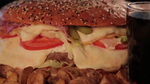 riesige leckere Burger mit Kartoffeln und sprudelndem Getränk.