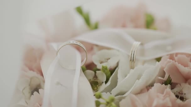 wedding bouquet with wedding rings on the table.
