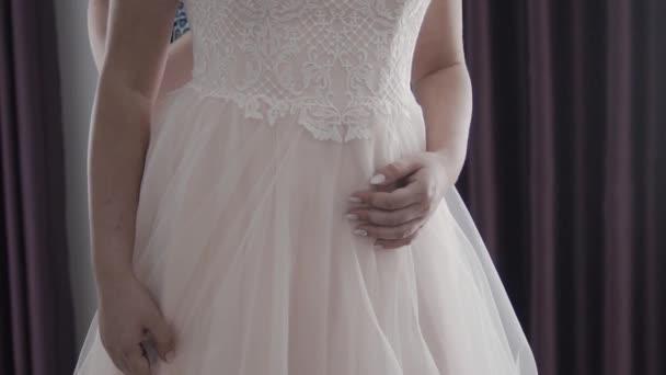 Zár-megjelöl-ból vissza a fiatal menyasszony esküvő készül. Anya lánya menyasszonyi ruha öltöztetős. Csipke és éves női kezek közelről. Valós időben teljes hd videó felvétel