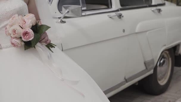 Nevěsta v krajkové šaty drží krásné bílé svatební kytice