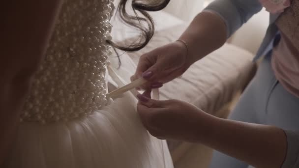 Close up of back of young bride getting ready for wedding ceremony. Mother helping her daughter to dress up bridal dress. Close up of lace and aged female hands. Real time full hd video footage