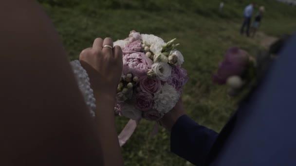 Beautiful newlyweds hold a wedding bouquet.