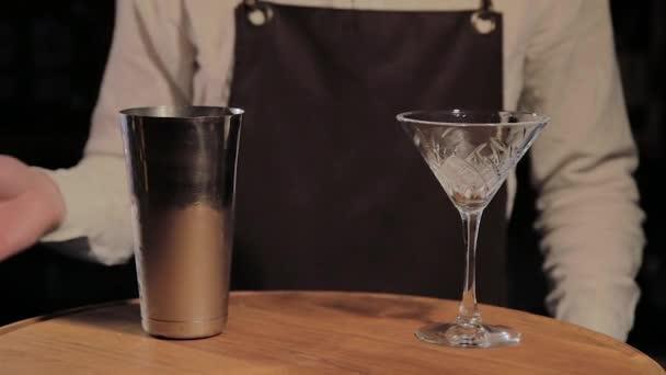 Proces přípravy alkoholického koktejlu v baru.