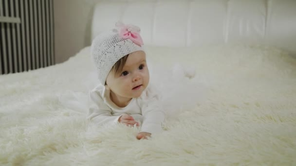 Krásná holčička leží na bílém lůžku.