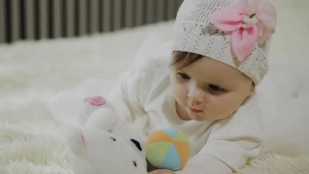 Beautiful little girl is lying on a white bed and playing with a toy