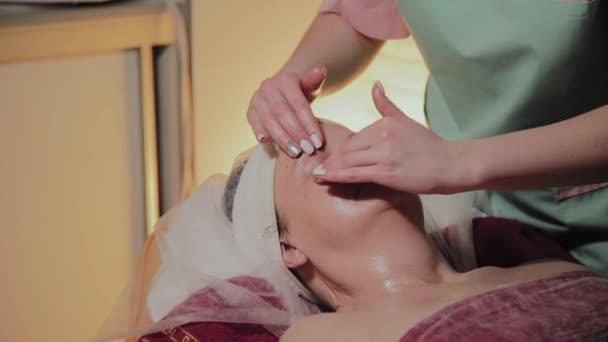 Profesionální kosmetolog dělá masáž staré ženě. Kosmetologické inovace