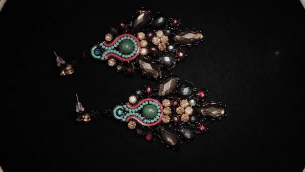 Beautiful female earrings on a black rotating stand. Premium Jewelery. Macro.