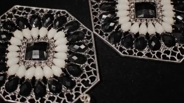 Překrásné ženské náušnice na černém otáčejícím se stojanu. Zlatoklenotství. Makro.
