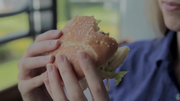 Krásná holka sní hamburger. Restaurace rychlého občerstvení