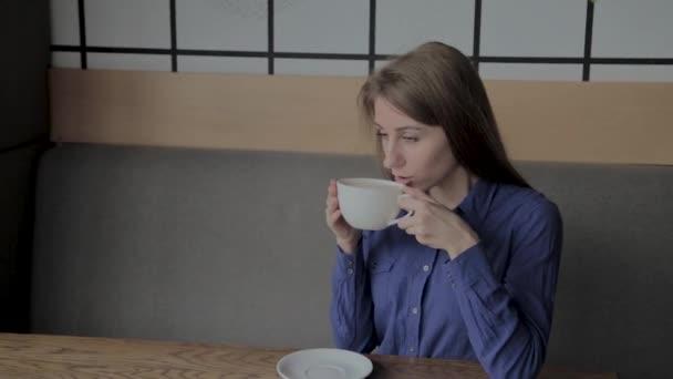Egy gyönyörű lány ül egy kávézóban, és kávéfogyasztás.