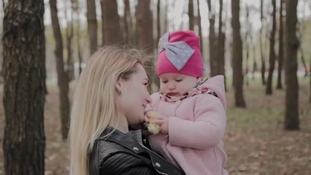 Krásná matka, držící v parku dívku v náručí.
