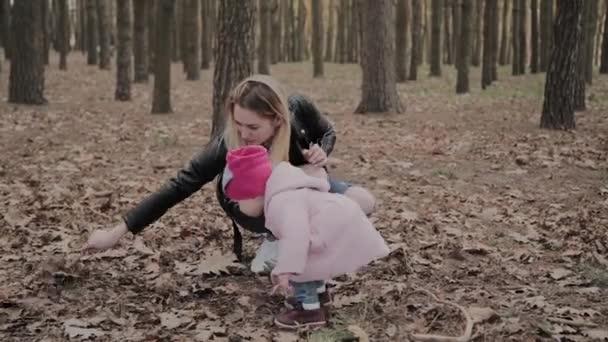 Šťastná máma s dcerou chodí do parku.