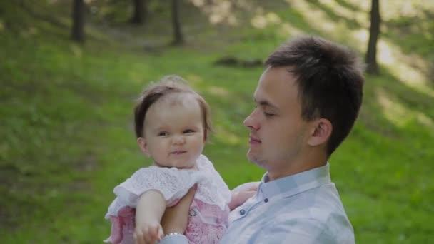 Fiatal apa a karjaiban tartja a babát..