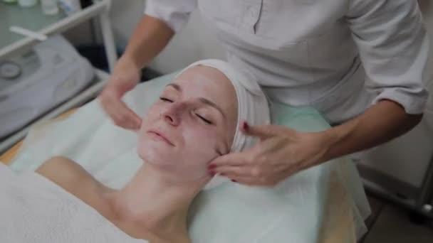Cosmetologo professionista che fa massaggi facciali nel salone di bellezza.