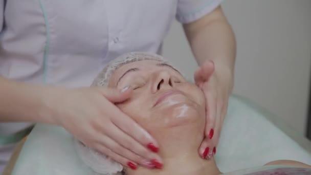 Női kozmetológus csinál arcmasszázs idős nő kozmetológiai Klinika.