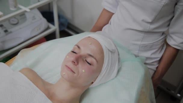 Profesionální kosmetolog aplikuje zvlhčovadlo na obličej.