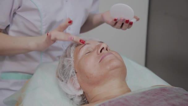 Szakmai kozmetikus vonatkozik védőkrém az idős nő a szépségszalonban.