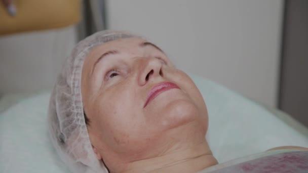 Kozmetikus eltávolítja a smink, hogy egy idős nő a kozmetológiai klinikán.