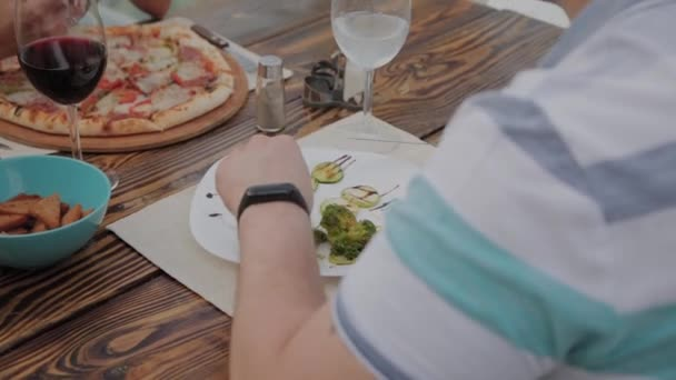 Egy fiatal férfi ebédelni egy salátával és zöldségekkel egy étteremben a nyitott teraszon. Egészséges táplálkozás.
