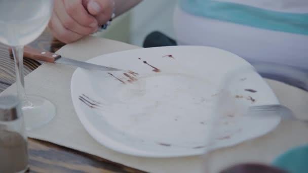 Mladý muž položil talíř se salátem na stůl v restauraci.