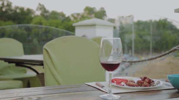 Mladý muž sedí u stolu v restauraci na terase..