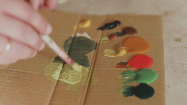 Artista mescola vernici sulla tavolozza prima di dipingere un quadro, pittore presso lo studio, creatore fa opera darte.