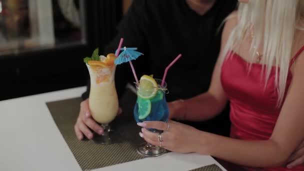 schönes Mädchen und Mann mit frischen Cocktails im Abendcafé.