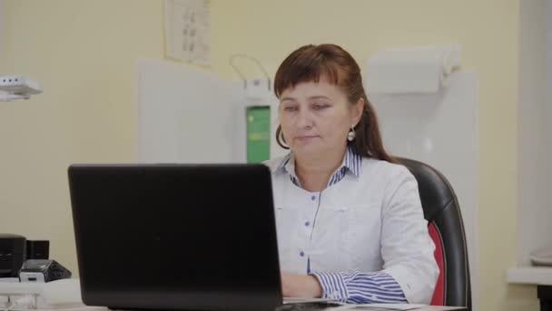 Starší lékařská žena pracující v počítači na klinice.