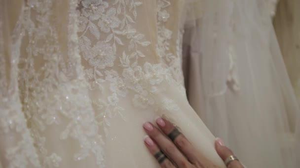 Krásná dívka si vybírá svatební šaty v svatebních kadeřnictví.